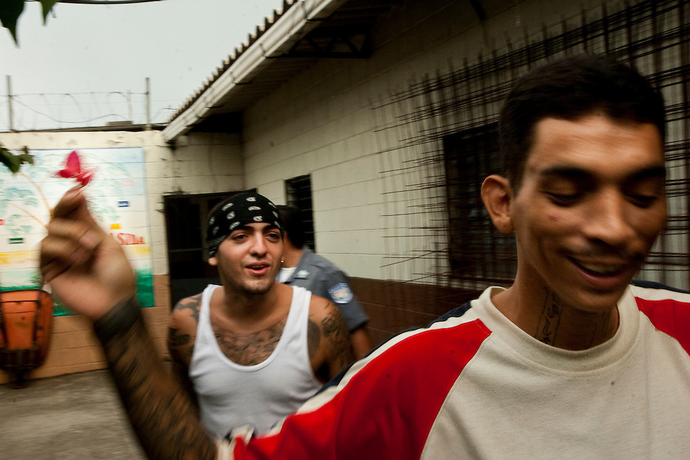 "Anthony Javier Pleiez (left) and Coistian Omar Scopa (right) in the lowest security section of Cojutepecque prison.  Pleiez says his 18th street clique protects his community. ""We are a united gang If we are going to do something we have to come to a conclusion with all the family, because here there is no leaders . Our gang depends on nobody, we are all here because we all care for each other.  We identify with the barrio where we live.  With the other gang (MS-13) , they have problems because the community does not like them.  I don't like the other gangs because they are disturbing the community and robbing and all that shit. We are in charge to look after the people in our barrio."""