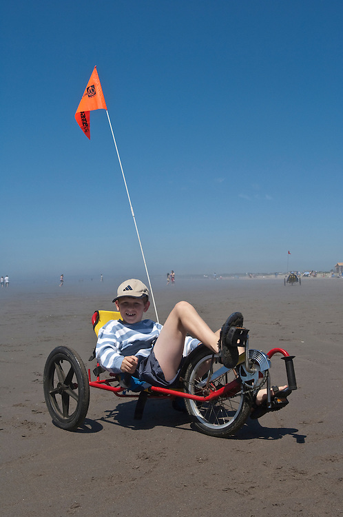 Boy riding peddle trike on the beach at Seaside, Oregon.
