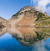 Del Campo Peak rises above Foggy Lake in Gothic Basin, in the Cascade Mountains of Washington, USA. Hike 10 miles round trip with 3300 feet gain along a mostly steep and rough trail, starting from the trailhead at Barlow Pass on the Mountain Loop Highway, 20 miles east of Verlot Visitor Center, in Mount Baker - Snoqualmie National Forest. Stitched from 2 images.
