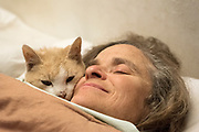 Woman and cat snuggling in bed.
