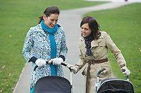 Two mothers in park looking at their babies in strollers