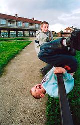 Boys playing near shops on run down council estate; Bradford UK