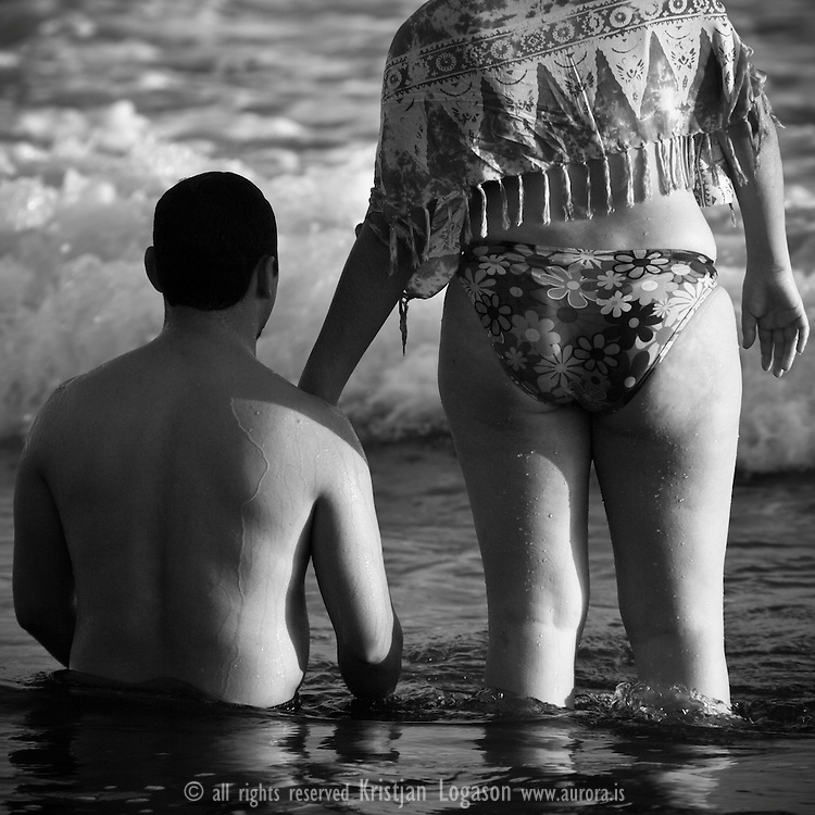 Romantic couple in the waves at El Tunco Beach in El Salvador on New years day