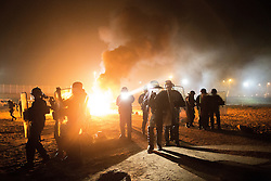 """© Licensed to London News Pictures . 23/10/2016 . Calais , France . Riot police in front of a fire set by residents , at the Calais migrant camp known as """" The Jungle """" , in Northern France , on the evening before the start of the eviction and destruction of the camp . Photo credit: Joel Goodman/LNP"""