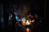 Men heating up near a fire in the Al Shate' refugee camp north of Gaza City. Uomini si riscaldano vicino un fuoco nel campo rifugiati di Al Shate' a nord di Gaza City.