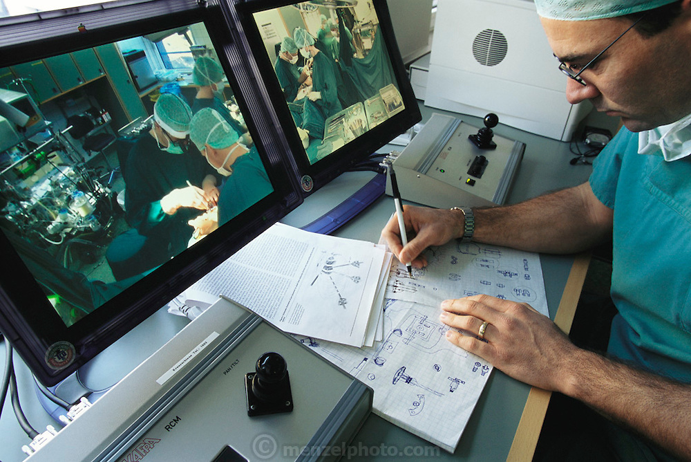 Engineer Chris Julian of robotic surgical systems company, Intuitive Surgical of Mountainview, California, watches heart surgeons perform robotic cardiac surgery and sketches improvements and modifications to the system. Herzzentrum Heart Center, Leipzig, Germany