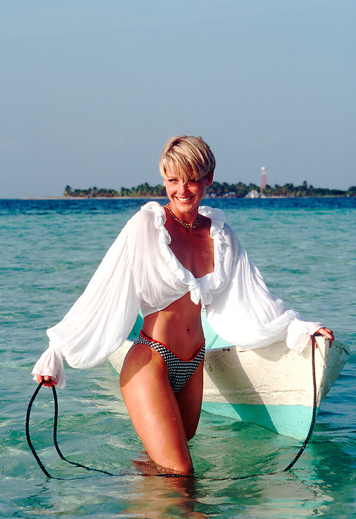 Young blond woman, 25-30, walking in ocean with colorful dugout canoe.