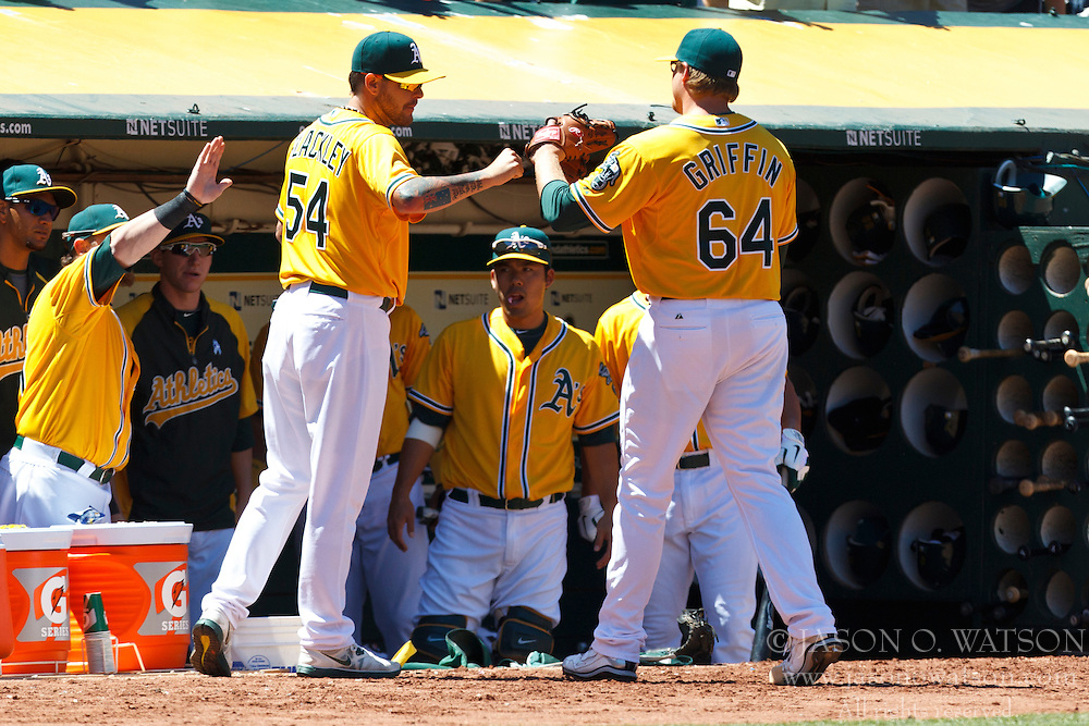 OAKLAND, CA - JUNE 24: A.J. Griffin #64 of the Oakland Athletics is congratulated by teammates in the dugout after being relieved during the seventh inning of an interleague game against the San Francisco Giants at O.co Coliseum on June 24, 2012 in Oakland, California.  The Oakland Athletics defeated the San Francisco Giants 4-2. (Photo by Jason O. Watson/Getty Images) *** Local Caption *** A.J. Griffin