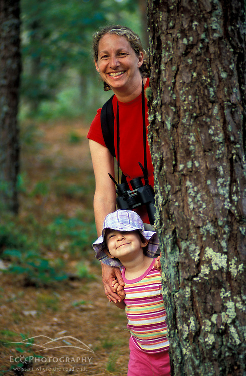Harwich, MA..A woman and her daughter play peekaboo from behind a pitch pine tree near the Monomoy River (a.k.a. Muddy Creek) in Harwich on Cape Cod.