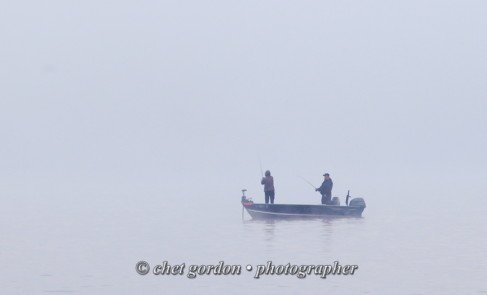 Two fishermen work in the fog on Greenwood Lake, NY on Sunday morning, October 16, 2016.  © Chet Gordon • Photographer