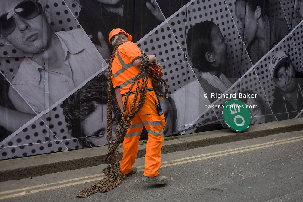 A construction site contractor drops heavy chains that he's been carrying along the street, in front of a hoarding featuring many faces.