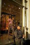 A man waits near a Victoria Secret's storefront.