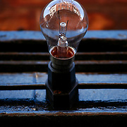 A lightbulb from a shop sign, show the reflections of the Dublin City street when taken in close up