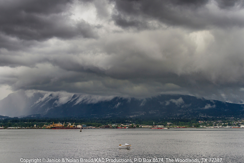 Seaplane taking off in rain storm over Vancouver Harbor.