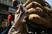A Pukhtun laborer pushes a cart with bags full of grain at a wholesale market in Karachi, Pakistan.
