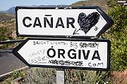 Graffiti on road signs for Orgiva and Canar, Alpujarra area, Granada province, Spain