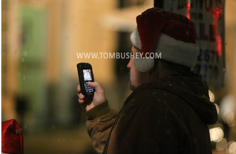 Pine Bush, NY - A man wearing a Santa hat records a scene with his cell phone camera during the Pine Bush Festival of Lights on Dec. 5, 2009.