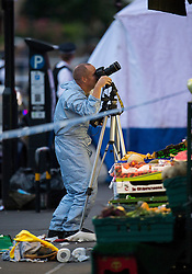 © Licensed to London News Pictures. 10/07/2015. London, UK. A forensics officer taking pictures while standing over a shoe and  bloodied clothing. Police and forensics forensics at the scene of a double shooting on Lordship Lame in Wood Green, north London in which a man has died and a woman is currently being treated in hospital.  Photo credit: Ben Cawthra/LNP