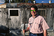 Frank Ochmann, Stern Magazine writer wearing bug glasses, by old trailer on ranch, Roswell, New Mexico. Model Released (1947 UFO Incident.)  (1997).
