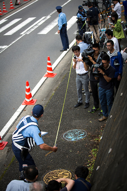 SAGAMIHARA, JAPAN - JULY 27 :  Police investigators measuring the distance of a found object from the post dropped by the suspect in front of the entrance of Tsukui Yamayuri-en building at Sagamihara on Wednesday, July 27, 2016 in Kanagawa prefecture, Japan. Police arrested 26 year old Satoshi Uematsu after breaking inside the building facility for handicapped and killing 19 people and injuring 20 in the city of Sagamihara, west of Tokyo. (Photo: Richard Atrero de Guzman/NURPhoto)