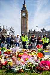 © Licensed to London News Pictures. 25/03/2017. London, UK. Members of public and police officers pay their respects to the victims of Westminster terror attack in Parliament Square, London on 25 March 2017. Photo credit: Tolga Akmen/LNP