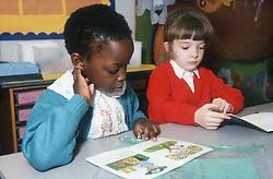 Nursery school boy and girl reading story books in classroom,