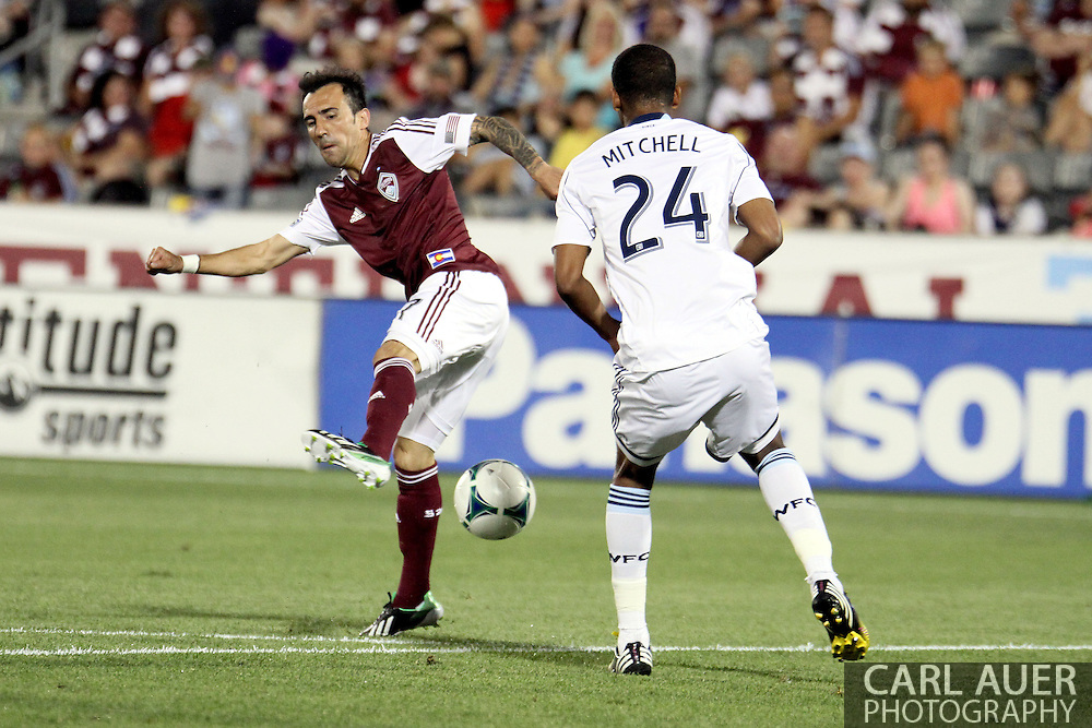 August 17th, 2013 - Colorado Rapids forward Vicente Sánchez (7) attempts to pass the ball backwards past Vancouver Whitecaps FC defender Carlyle Mitchell (24) in the second half of the Major League Soccer match between the Vancouver Whitecaps FC and the Colorado Rapids at Dick's Sporting Goods Park in Commerce City, CO