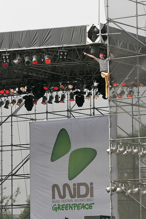 A performer jumps from stage and climbs the scaffolding during the Midi Festival in Beijing China 2007.  Midi is an  rock music festival held in northern Beijing catering to a small group of music listeners in China.  The festival lasts 4 days and gives performances from Chinese and international bands.