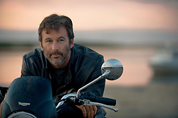portrait of a very rugged handsome man with a beard on a motorcycle