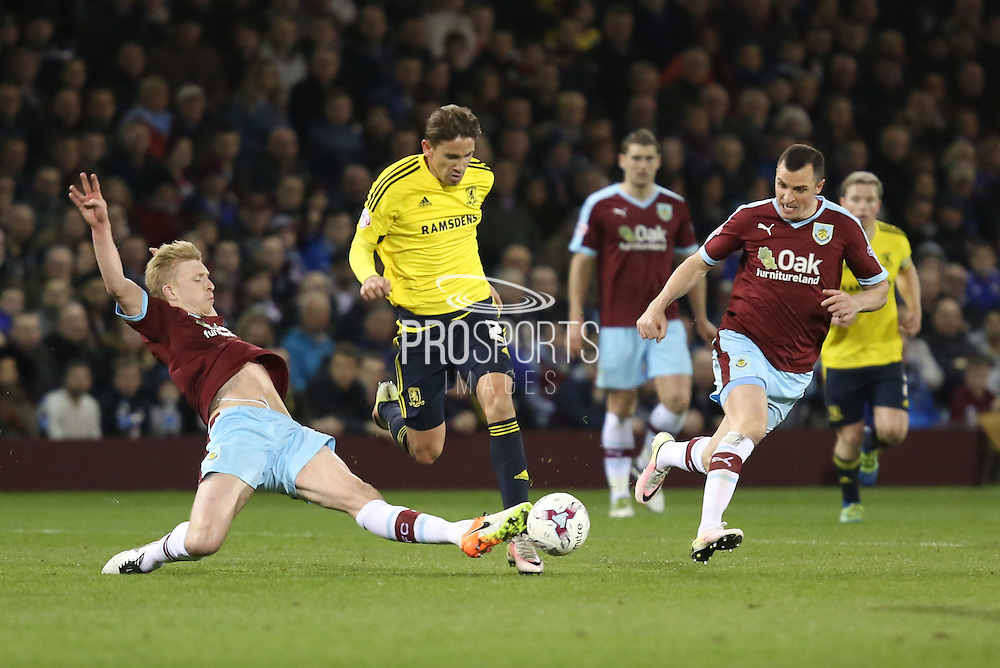 Ben Mee of Burnley makes a sliding challenge on Gaston Ramirez of Middlesbrough during the Sky Bet Championship match between Burnley and Middlesbrough at Turf Moor, Burnley, England on 19 April 2016. Photo by Simon Brady.