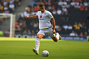 Milton Keynes Dons midfielder Jordan Houghton (24) takes a shot at goal during the EFL Sky Bet League 1 match between Milton Keynes Dons and Peterborough United at stadium:mk, Milton Keynes, England on 24 August 2019.