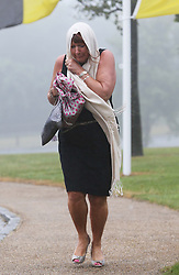Not so Glorious Goodwood… A race goer get's caught up in torrential rainfall as she arrives for  the opening day of Glorious Goodwood in the UK, Tuesday, 30th July 2013 <br /> Picture by Stephen Lock / i-Images