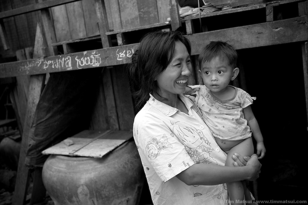 "Prostitute Wue holds a baby at home in a slum where the non governmental organization ""Acting for Women in Distressing Situations"" (AFESIP), conducts outreach and provides services in Phnom Penh, Cambodia. The permanent structure, a decaying four story building known simply as 'The Building', was built in the 1960's as transitional housing and now hosts a shantytown where many of the city's poor live, including many prostitutes, and is believed to have the highest rate of HIV infection in the city. AFESIP hands out free condoms, instructs prostitutes on HIV prevention, and conducts outreach in case the prostitutes need medical services, choose to leave their profession, or can report on cases of sex trafficking. AFESIP offers housing, education, training, and counseling for women who are victims of sex trafficking, worked as prostitutes, or are escaping domestic violence. Founded by Somaly Mam, who herself was once a prostitute and victim of trafficking and domestic abuse, AFESIP has three facilities in Cambodia and works with other NGO's to provide long term care for the women."