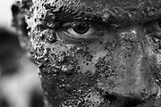 """Pablo Fernando, a member of one of the jerico teams, shows his face covered in mud after the trainings for the Grand Prix in Alto Paraiso, Brazil, on Saturday, Feb. 16, 2008. ..:: BRIEF CONTEXTUALIZATION ::..Once a year, the small city of Alto Paraiso becomes the ultimate destination for all the motor enthusiasts in the Amazon area. With only 6,500 habitants in its urban area, every February the city becomes densely packed with more than 45,000 visitors coming from all over the region, a multitude of men and women united by their passion for music, mud and diesel smoke..In a race track made of dirt and water from the abundant Amazonian rains, vehicles which seem to come from a Hanna & Barbera cartoon dispute, from mud puddle to mud puddle, the most exotic grand prix of the Brazilian automobilism. While the high and typical roar of their stationary motors echoes all over the """"autodrome"""", the jericos* and its pilots fight amidst lots of smoke and mud in the eyes for a better performance in the narrow and slippery circuit of Alto Paraiso. Every victory, every passing is effusively celebrated in dionysiac mud baths..By the end of the week, the peaceful city in the heart of the Amazon Forest goes back to normality and the jericos*, once fast and furious machines, are back again to the calm rhythm of the countryside, carrying the heavy weight of life over their trunks...* Jerico is the suggestive name of this makeshift vehicle, very popular in the Amazon and famous for its capacity of carrying weight. Meaning mule in Portuguese, these machines are commonly built by putting together a steering wheel, a junked chassis and a mining pump engine."""