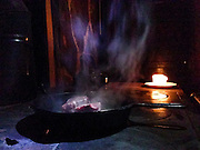 Lamb steaks cooking in a cast iron skillet on a wood burning stove during a power outage in the winter at Sam Barker's home.