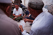 Kashgar: Uighur men play cards on the street in Kasghgar...Despite the migration of millions of Han Chinese to the western part of the Xinjiang Uighur Autonomous Region, the Uighur community continue to practice their muslim culture and resist the suppression of their cultural and religious traditions by the Chinese government....The chinese government has been criticised for the redevelopment of the old city, which has involved the destruction of many of the old houses in the town that were built without regulation, officials claiming them to be overcrowded and uncompliant with earthquake codes...Many in the chinese government believe Kashgar to a breeding ground for Uighur separatists, who Beijing claim to have links to terrorism...The european parliament has called for a halt to the cultural destruction of Kashgar, suggesting that Kashgar be added tot he UNESCO World heritage 'Silk Road' project, and calling on the chinese government to develop a genuine Han-Uighur dialogue to adopt more inclusive and comprehensive economic policies in Xinjiang in order to protect the cultural identity of the Uighur population..©JTanner/July 2011