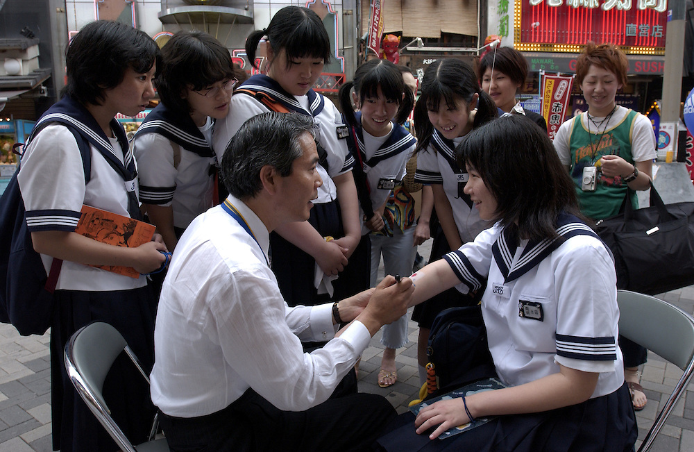 Japanese schoolgirls show their support for the Japanese soccer team during Japan's hosting of the World Cup by having the team's colours painted on their arms. Tokyo June 2002..©David Dare Parker/AsiaWorks Photography