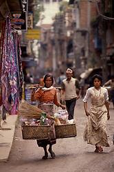 KATHMANDU, NEPAL - OCTOBER 1992 - a Nepalese merchant carries her wares through the streets of Kathmandu. (PHOTO © JOCK FISTICK)