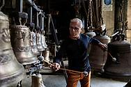 Agnone, Molise - Giulio Costanzo, composer and percussionist, tests the sound of some bells inside the Marinelli pontificial Foundry in Agnone.<br /> <br /> Ad Agnone, la tradizione di forgiare e fondere i metalli rislae a 2500 anni fa, al Medioevo. La fonderia Marinelli, con oltre otto secoli di attivit&agrave;, &egrave; l&rsquo;officina in cui vengno prodotte camoane pi&ugrave; antica del mondo. Ad oggi i Marinelli continuano questa secolare tradizione forgiando campane dai bellissimi rilievi artistici e dalla perfetta sonorit&agrave;. Nel 1924, Papa Pio XI, concesse alla famiglia Marinelli di effiggiarsi dello stemma Pontificio.<br /> Ph. Roberto Salomone