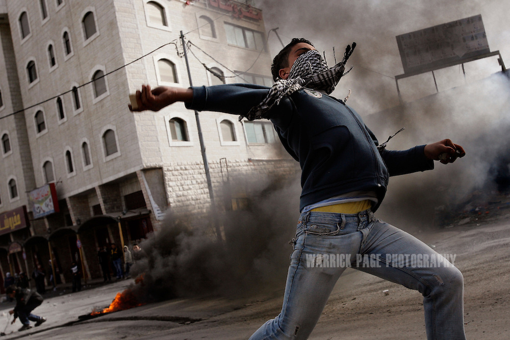 WEST BANK, PALESTINIAN TERRITORIES - JANUARY 16: A Palestinian youth throws a rock at Israeli border police during clashes in Shuafat refugee camp, January 16, 2009, West Bank, Palestinian Territories. Israeli police closed the Al Aqsa Mosque to Palestinian males aged 15-50 fearing the current invasion of Gaza would spark violence in Jerusalem. More than 1000 Palestinians have been reportedly killed and 13 Israelis as the conflict enters it's third week as Israeli military forces continue to pound Gaza and step up operations in urban areas. The UN continues to call for an immediate ceasefire, as the secretary general of the UN, Ban Ki Moon visits Israel to urge both sides in ending the conflict. The Israeli chief negotiator, Amos Gilad, is visiting Cairo to discuss an Egyptian ceasefire plan that could see a peacekeeping force responsible for preventing arms smuggling on the Gaza/Egypt border. (Photo by Warrick Page)