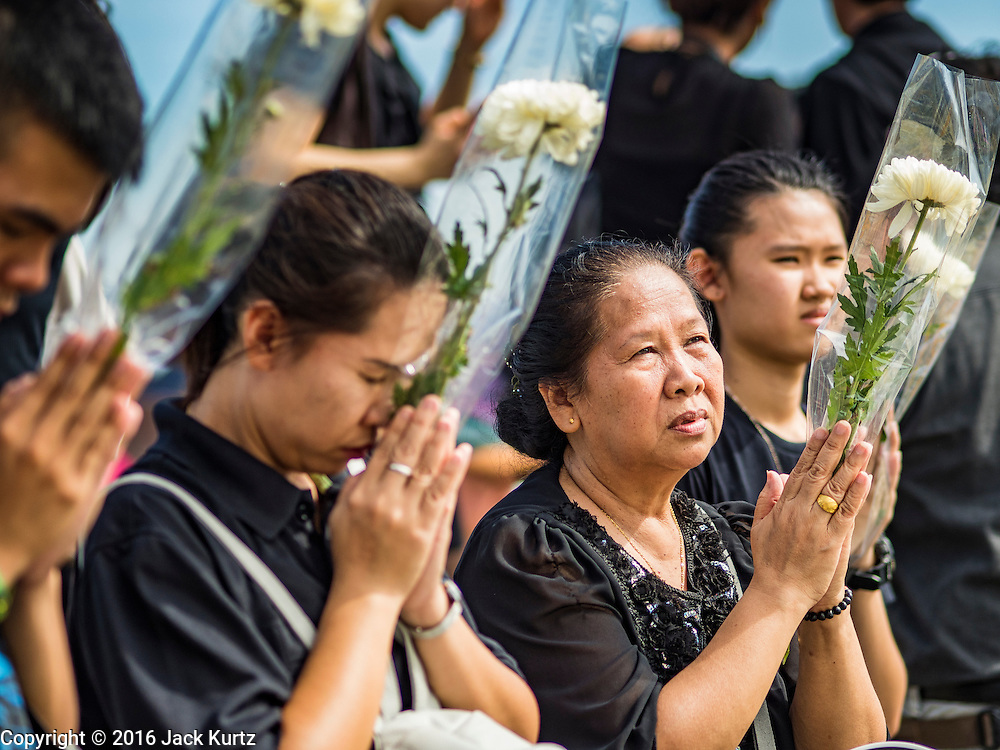 22 OCTOBER 2016 - BANGKOK, THAILAND:  People with flowers pray for the late Bhumibol Adulyadej, the King of Thailand, at Sanam Luang Saturday. Sanam Luang, the Royal Ceremonial Ground, was packed Saturday with more than 100,000 people mourning the Monarch's death. The King died Oct. 13, 2016. He was 88. His death came after a period of failing health. Bhumibol Adulyadej was born in Cambridge, MA, on 5 December 1927. He was the ninth monarch of Thailand from the Chakri Dynasty and is also known as Rama IX. He became King on June 9, 1946 and served as King of Thailand for 70 years, 126 days. He was, at the time of his death, the world's longest-serving head of state and the longest-reigning monarch in Thai history.      PHOTO BY JACK KURTZ