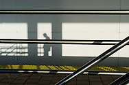 Shadows of commuters waiting to catch a train at a station in Miami Beach, Florida