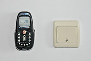 Airconditioner remote control and light switch on white background
