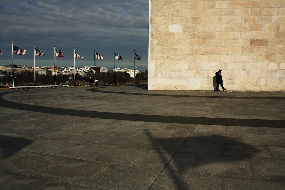 A security guard walks by the Washington Monument in Washington, DC on January 21, 2006.