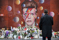 © Licensed to London News Pictures. 10/01/2017. London, UK. Floral tributes are placed at a mural and shrine to David Bowie in Brixton on the first anniversary of his death. David Bowie was born in Brixton, south London. Photo credit: Peter Macdiarmid/LNP