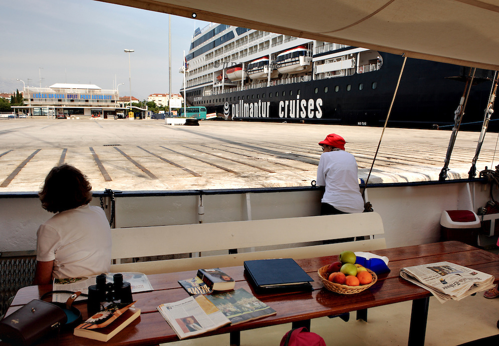View from the deck of a 12 passenger sailing schooner docked at Split alongside a massive cruise ship carrying thousands.  The contrast in size and scale is tremendous. Two adult women lounge on the schooner.  The dock is empty except for a green bus pulling away from the cruise ship.