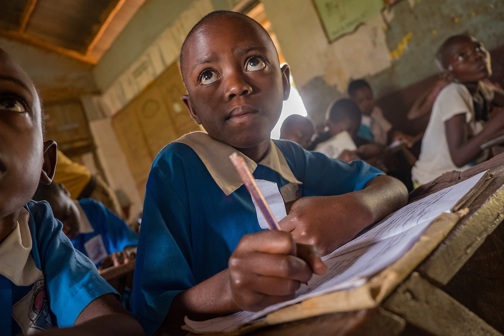 CAPTION: Juliet is an active participant in her class. Since being screened by SignHealth Uganda and having her hearing impairment detected and treated, her academic progress has improved and she has become more confident and involved in classroom activities. She answers questions readily, and no longer cranes her neck in order to hear through her stronger ear. LOCATION: Butenga-Kibanda Primary School, Butenga Village, near Masaka City, Bukomansimbi District, Central Region, Uganda. INDIVIDUAL(S) PHOTOGRAPHED: Juliet Nassuna.