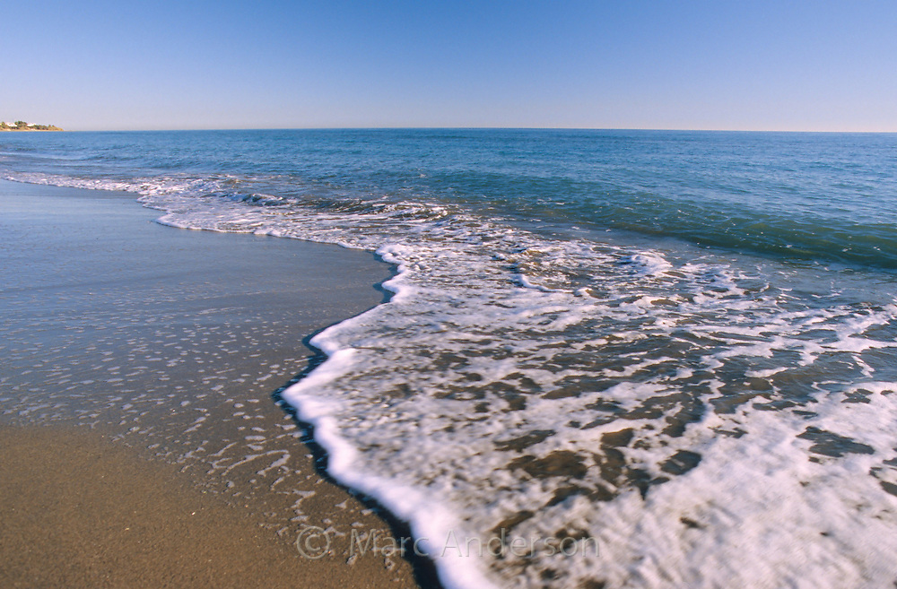 A small wave breaking on the shore of a sandy beach on the Costa del Sol, Spain