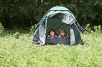 Portrait of two boys (7-9) lying in tent