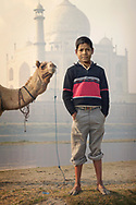 In Agra, India, a boy stands at the edge of the Yamuna River with his camel and the Taj Mahal looms behind him.